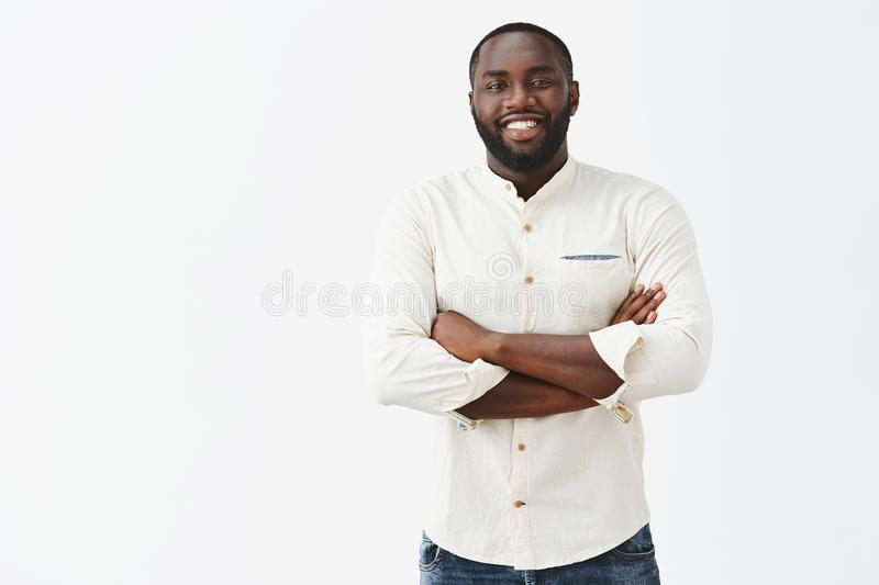 Satisfied African American man with beard looking and great result of personal efforts, being pleased and happy have royalty free stock images