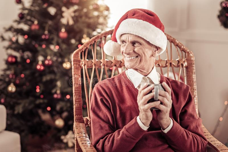 Satisfied aged man sitting and holding a cup. Waiting for wonder. Satisfied aged funny man in a red hat sitting in the chair near the Christmas-tree looking stock photography