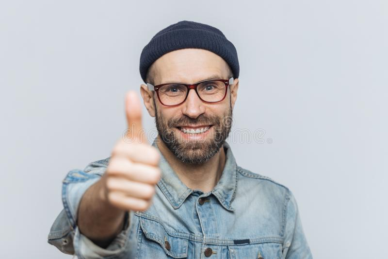 Satisfied attractive bearded male with happy expression, wears f stock images
