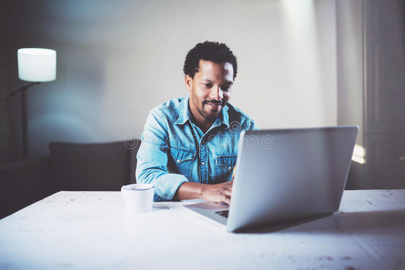 Satisfied bearded African man using laptop at coworking studio on the wooden table.Concept of young people work mobile stock images