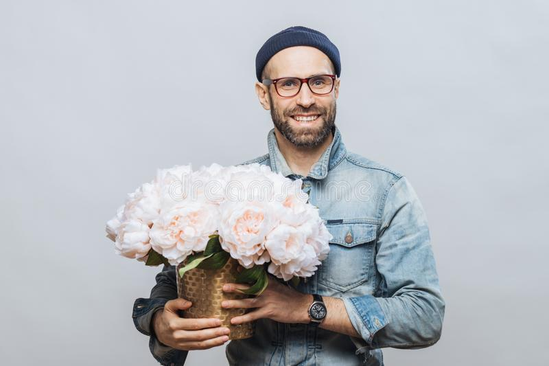 Satisfied bearded male with cheerful expression has broad smile, holds bunch of flowers, wears hat and denim jacket, isolated stock images