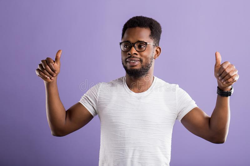 Dark skinned man  over purple background royalty free stock photography