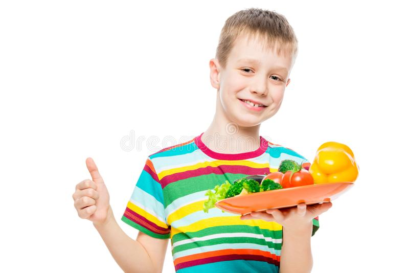 satisfied boy with a plate of healthy vegetables isolated on white background royalty free stock photos