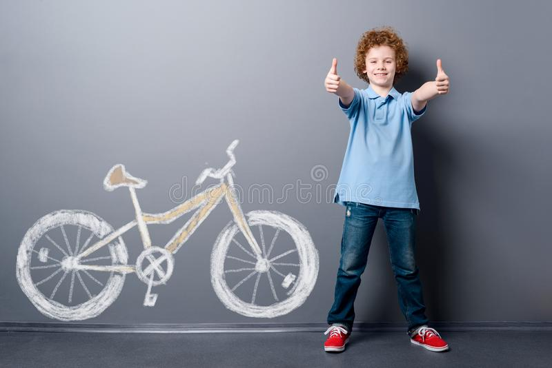 Satisfied boy and yellow bicycle. Happy child with curly red hair standing near gray wall with depicted dream royalty free stock photo