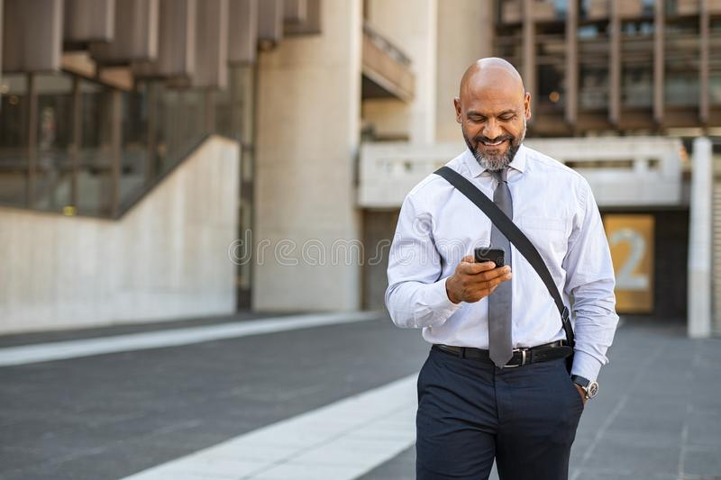 Satisfied businessman walking while using phone royalty free stock photography