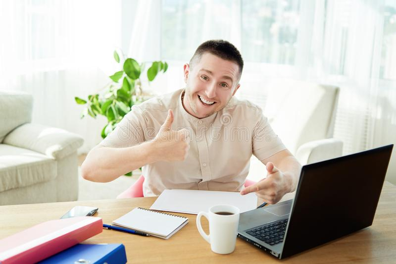 Satisfied businessman with work done in office. Happy young man working on laptop while sitting at workingplace stock image
