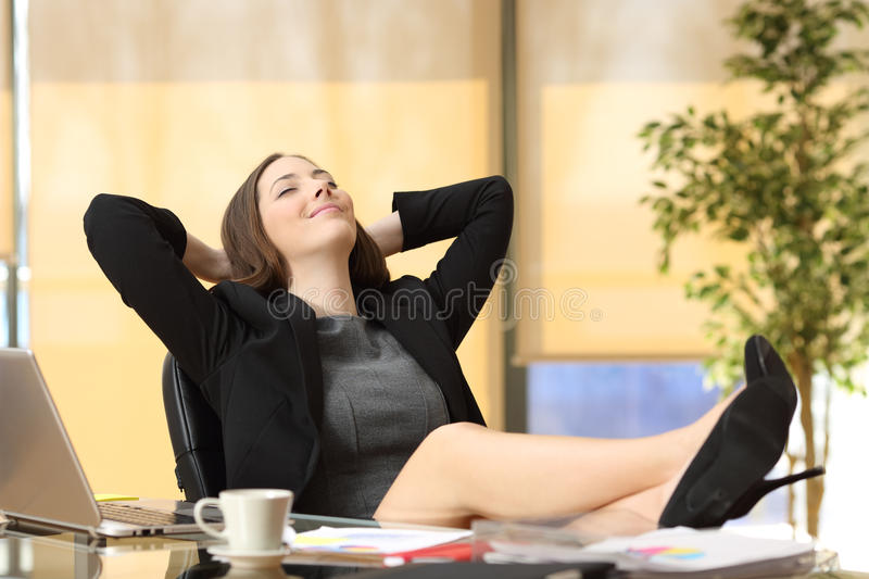 Satisfied businesswoman in her new job at office. Satisfied relaxed businesswoman sitting in a chair with legs over the table and hands in the head enjoying her stock photos