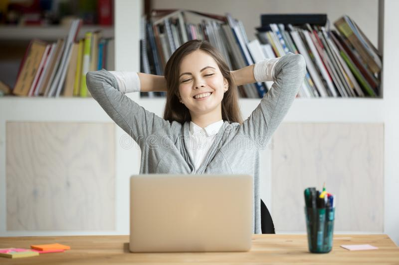 Satisfied female worker leaning in chair happy with company res stock photography