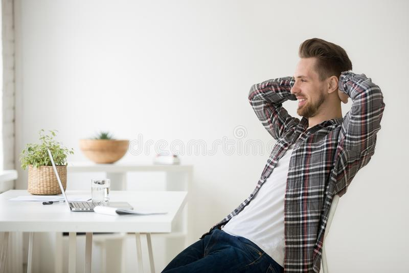 Satisfied Caucasian male relaxing in chair after finished work. Satisfied Caucasian man relaxing leaning back in chair hands over head, happy with work finished stock images