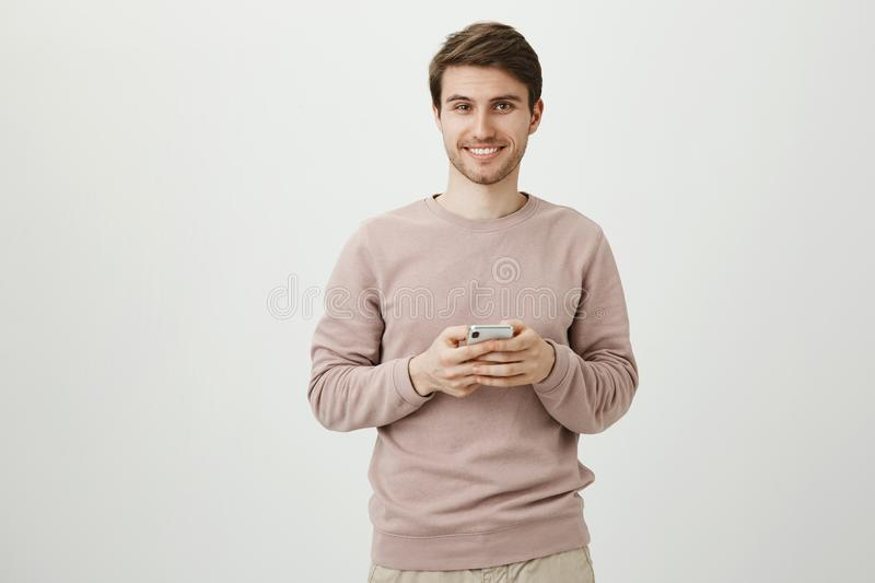 Satisfied charming man with bristle holding smartphone near chest, smiling and looking at camera, standing over gray. Background. Male was distracted from stock photos