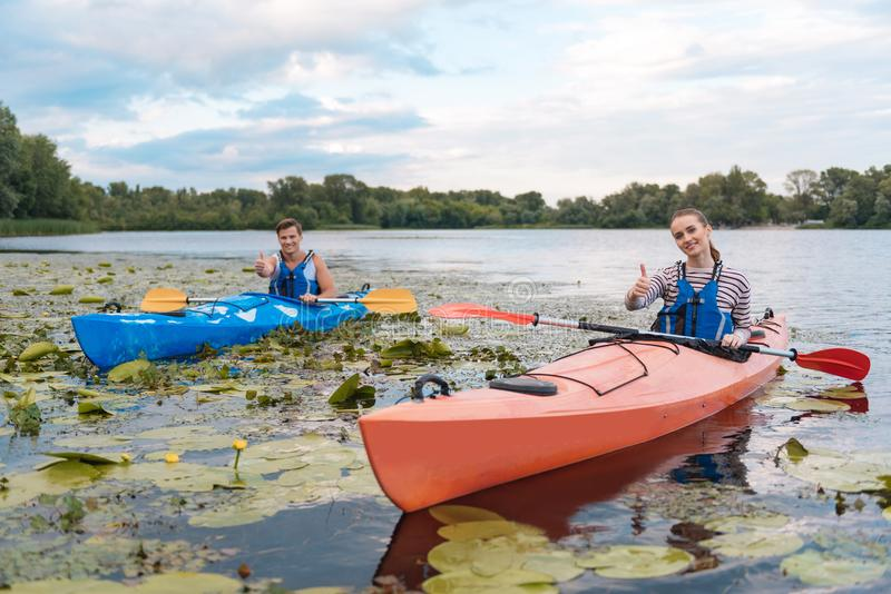Smiling couple feeling satisfied after active river ride in canoe royalty free stock photos