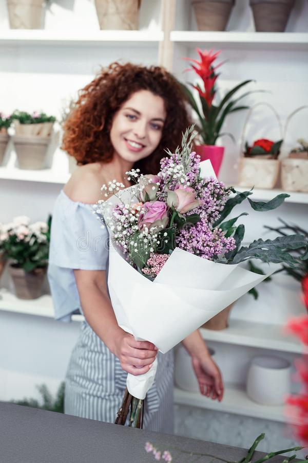 Satisfied curly-haired young girl showing her flower masterpiece stock images