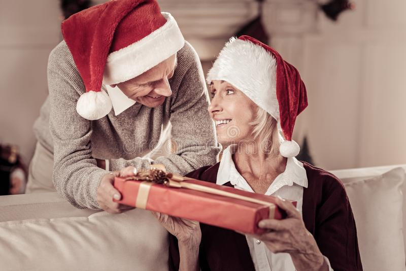 Satisfied cute woman holding a gift looking at her husband. Marry Christmas. Satisfied cute pleasant women in a red hat sitting on the sofa holding a gift and royalty free stock photo
