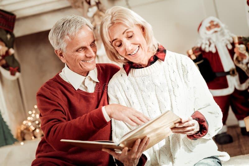 Satisfied envejeció a la mujer que sonreía y que mostraba un libro imágenes de archivo libres de regalías