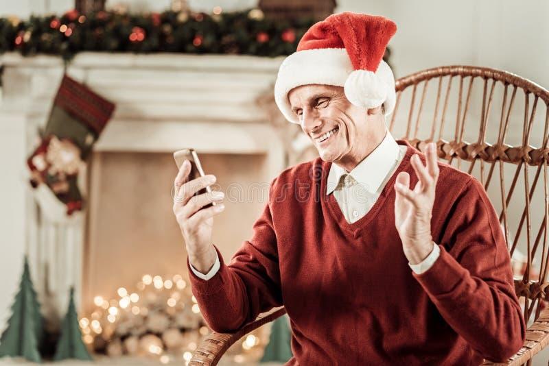 Satisfied envelheceu o homem que guarda o telefone celular e que agita a mão fotografia de stock royalty free