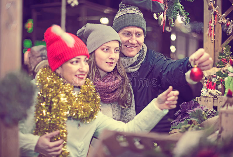 Satisfied family couple with teen daughter choosing Christmas de stock image