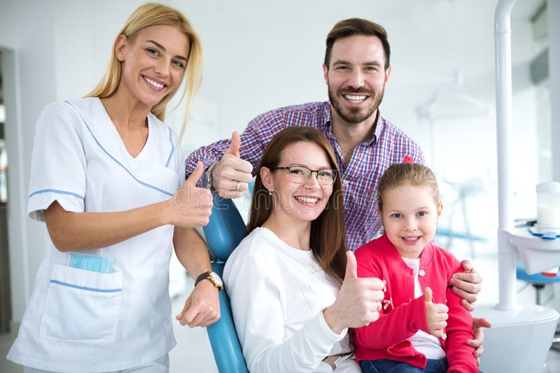 Satisfied family with a smiling young female dentist royalty free stock image