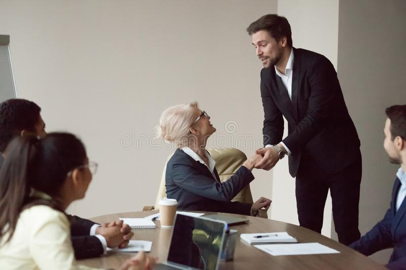 Satisfied grateful partner employee holding hand of executive expressing respect. Satisfied grateful partner employee holding shaking hand of executive thanking stock photos