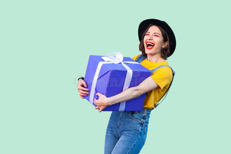 Satisfied happy beautiful young girl in hipster wear in denim overalls and black hat standing and holding big heavy gift box with royalty free stock photos
