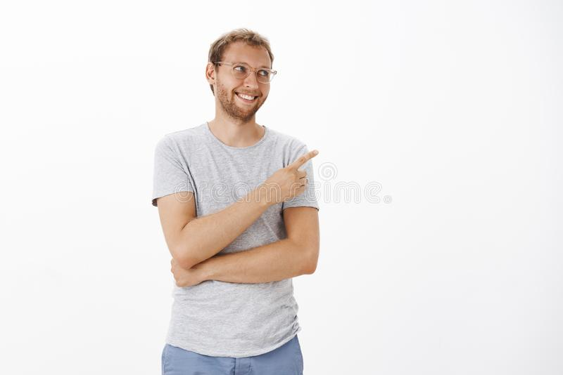 Satisfied happy cute european male model in glasses with bristle and fair hair smiling cheerfully pointing and gazing at royalty free stock photography