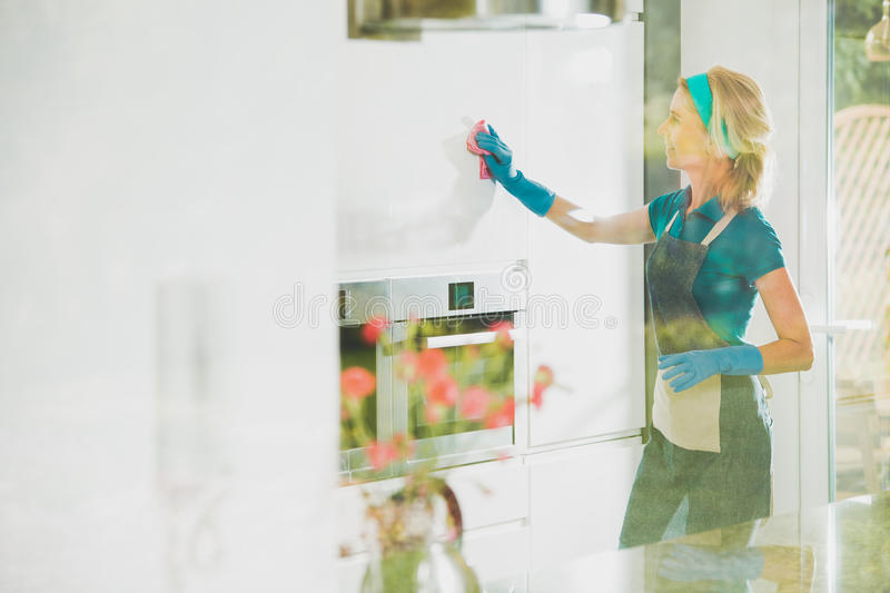 Satisfied housekeeper cleans. White shiny cabinets in blue rubber gloves and an apron stock images