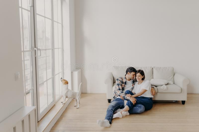 Satisfied husband and wife have romantic relationship, sit on floor near white couch in big room, wear jeans, tshirts and socks,. Spend leisure time in domestic royalty free stock images