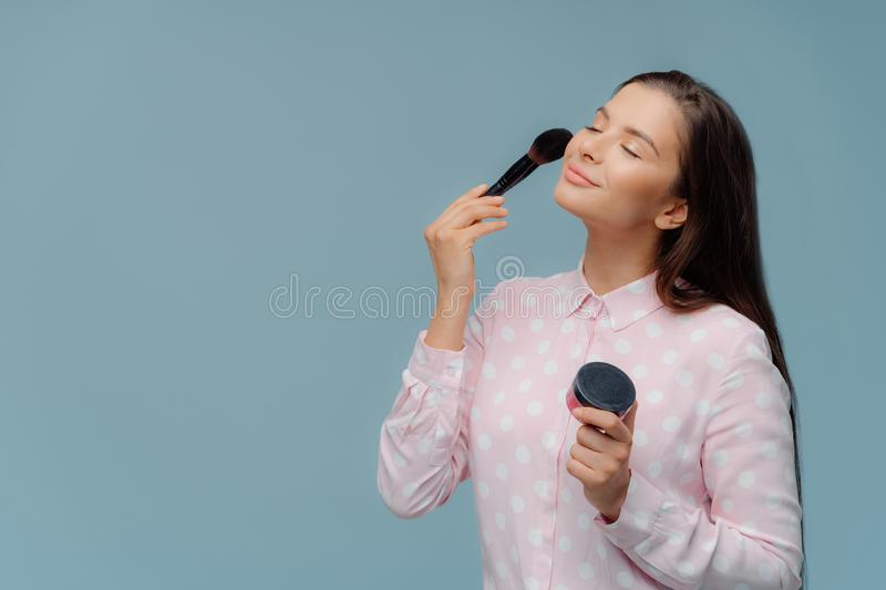 Satisfied lady applyes foundation with cosmetic brush, does professional makeup, wears elegant stylish shirt, models over blue. Background with copy space for stock image