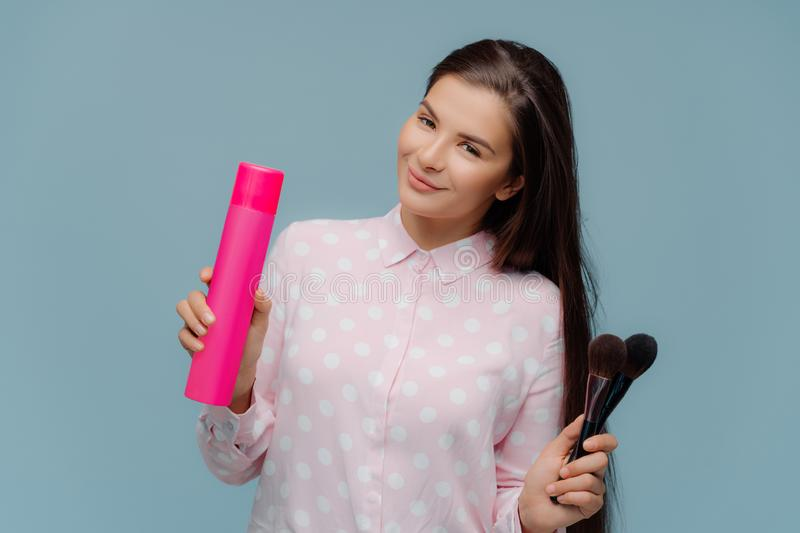 Satisfied long haired brunette female uses hairspray for making stylish hairdo, cosmetic brushes for applying powder on face, royalty free stock image
