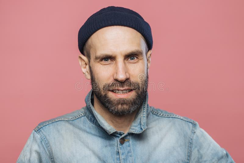 Satisfied male model with thick beard and mustache looks with confident expression into camera, wears fashionable hat and jacket, royalty free stock photo