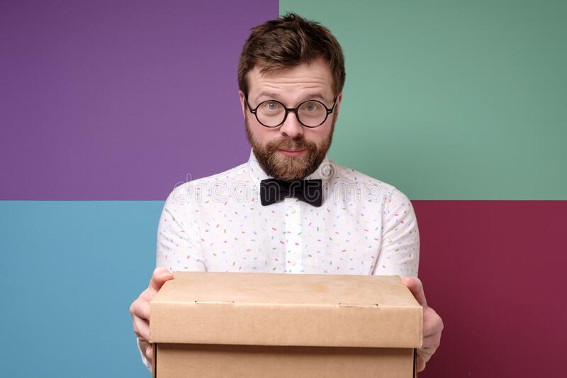 Satisfied man with round glasses holding a box and is looking forward to a pleasant surprise. royalty free stock photo