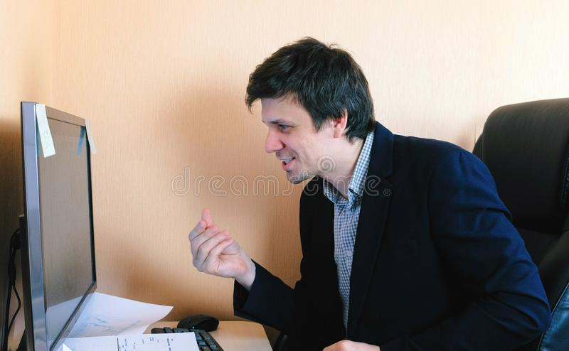 Satisfied man rubs his hands sitting on the computer. Work at the computer. stock photos