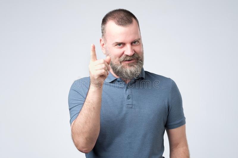Satisfied mature man in blue clothes showing index finger up royalty free stock photos