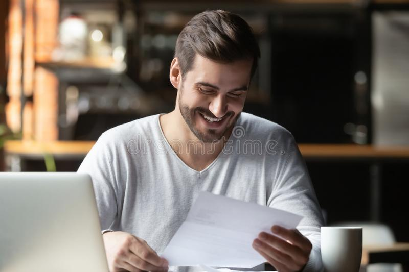 Satisfied millennial businessman reading paper letter with good news. Satisfied millennial businessman sitting in cafe near computer holding paper reading letter stock photography