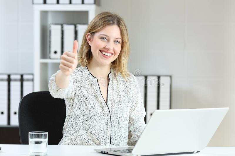 Satisfied office employee looking at you. Satisfied office employee looking at camera with thumbs up royalty free stock photography