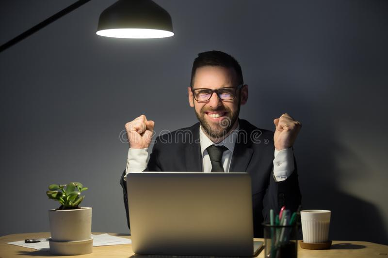 Excited male worker happy reading online news. Satisfied office worker happy with good results on stock market, making yes gesture, person winning online lottery royalty free stock photos