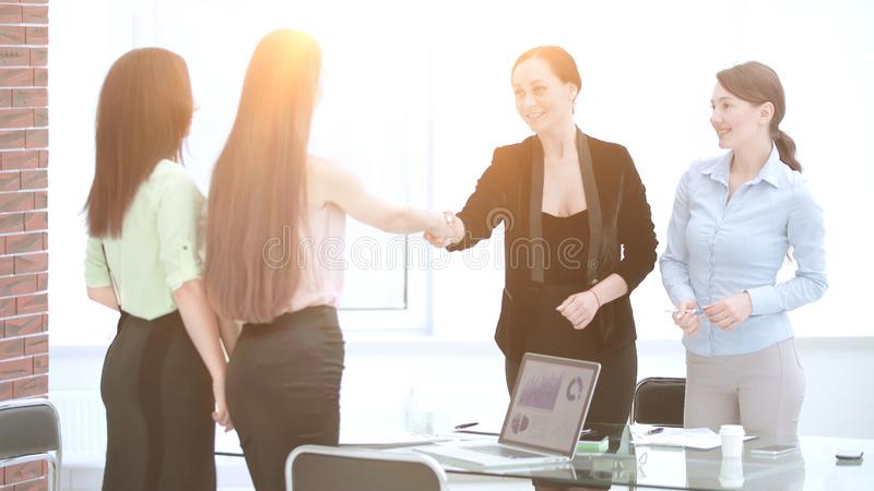 Satisfied older woman and young manager handshaking after signing contract in office stock photography