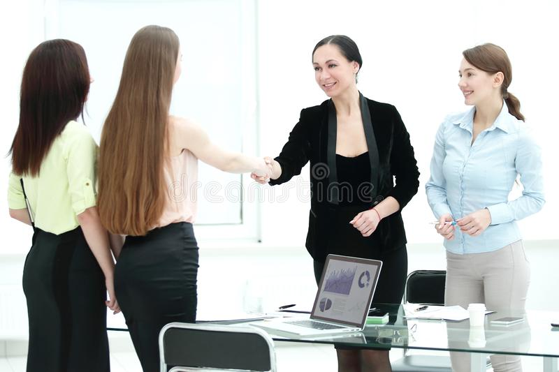 Satisfied older woman and young manager handshaking after signing contract in office. Satisfied older women and young manager handshaking after signing contract stock image