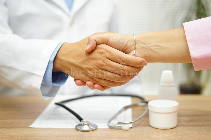 Satisfied patient is handshaking with good doctor over good heal. Th report stock photography