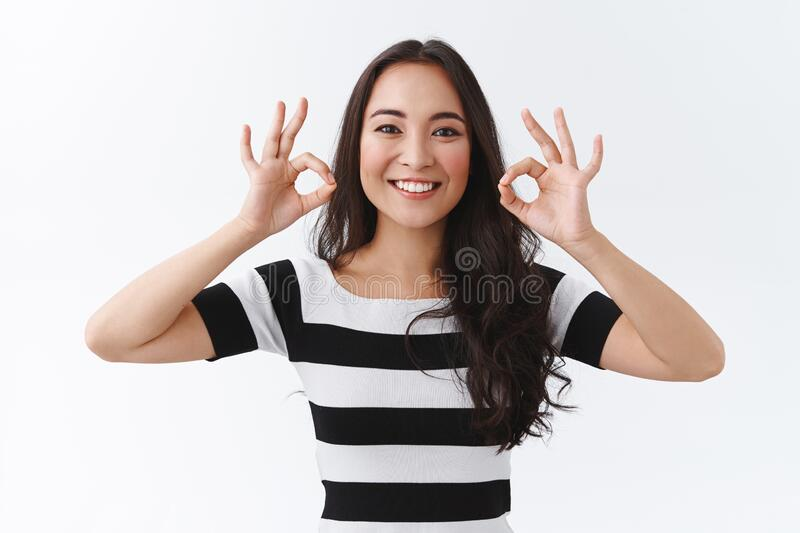 Satisfied pleasant and cheerful brunette east-asian woman in striped t-shirt keep everything under control, agree or stock images