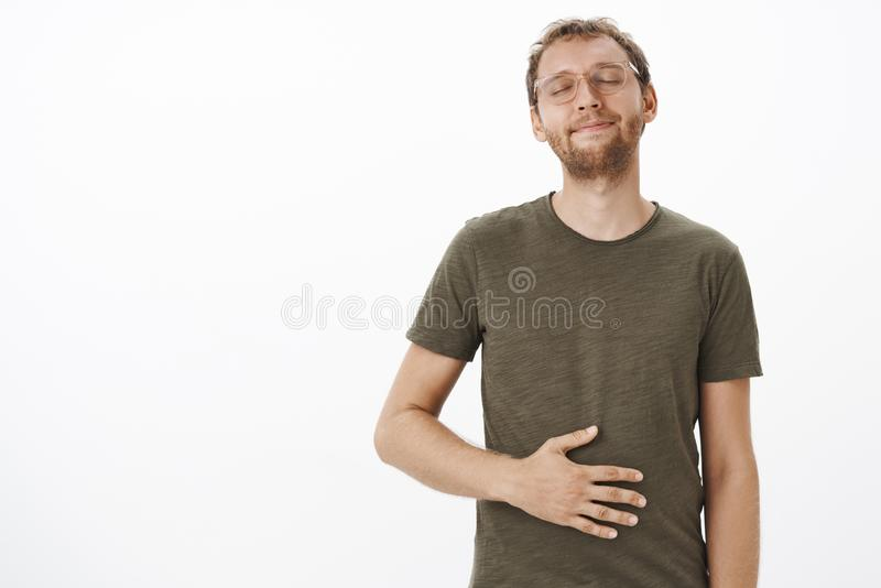 Satisfied and pleased male visiting favorite restaurant licking lips and closing eyes rubbing belly from delight and royalty free stock photos