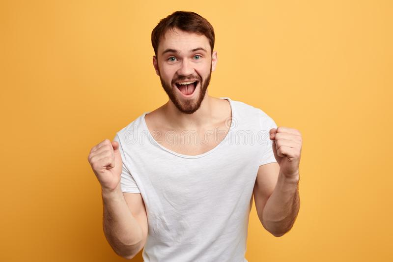 Satisfied positive young man celebrating success isolated over yellow background stock images