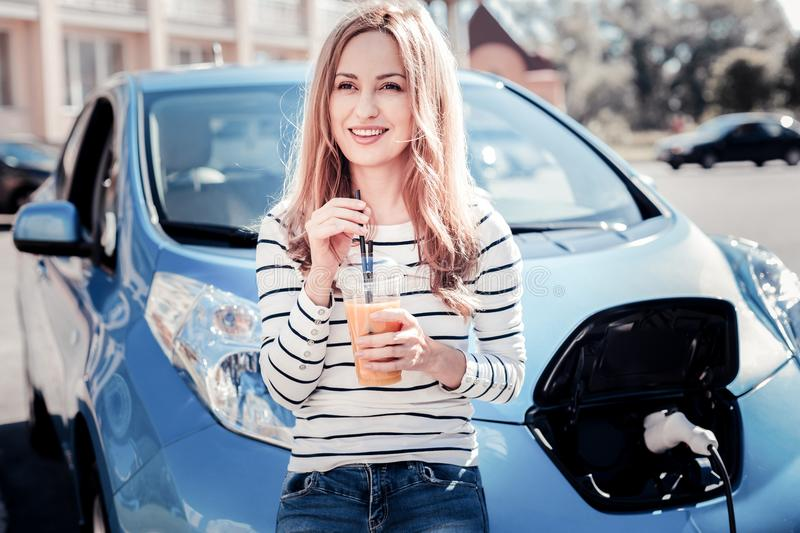 Satisfied pretty woman standing and drinking juice. royalty free stock images