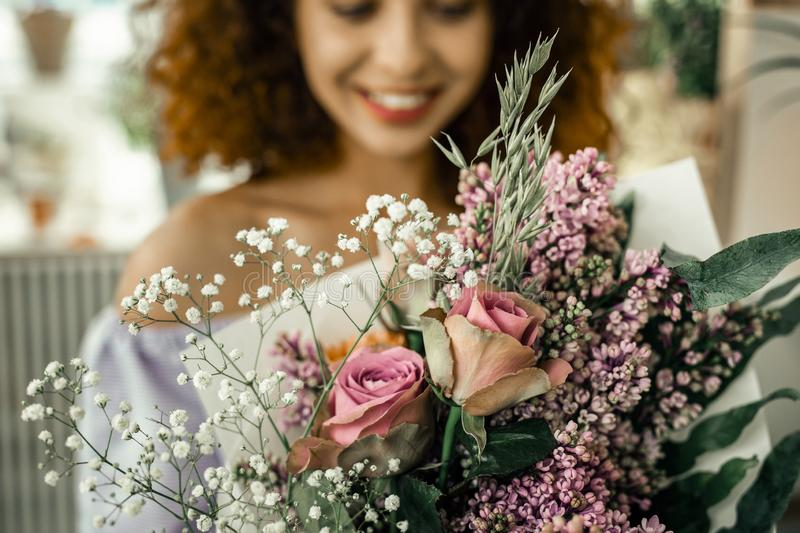 Curly florist wearing striped uniform feeling satisfied with result stock photo