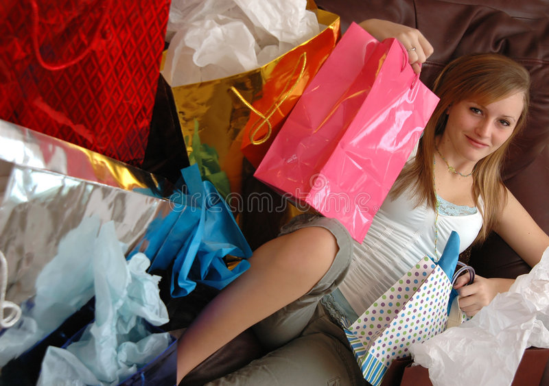 Satisfied shopper. A teen girl lying back on a couch with lots of shopping bags surrounding her