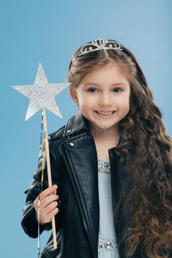 Satisfied small female child has long curly hair, dressed in black leather jacket, wears crown, holds magic wand, isolated over. Blue background. Dark haired stock images