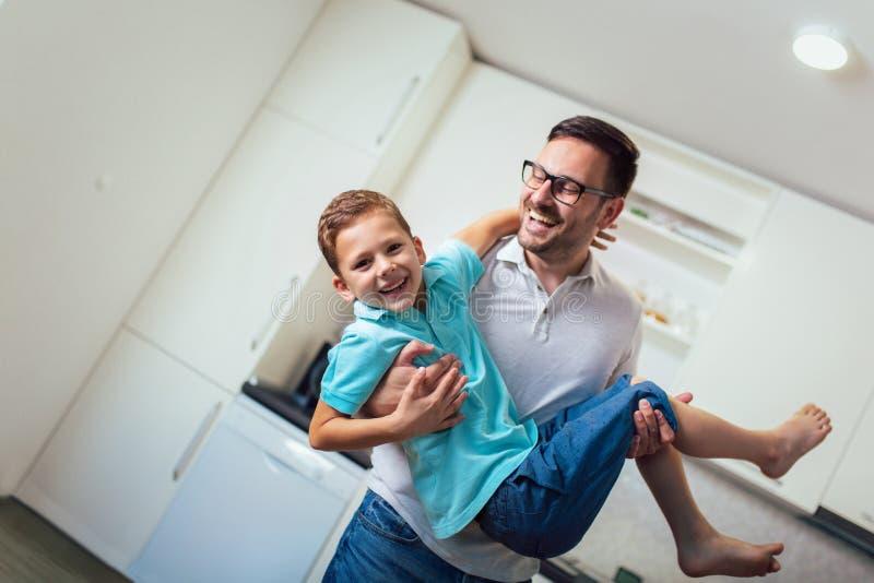 Satisfied smiling man piggybacking his son while having fun in modern studio apartment. Image of satisfied smiling men piggybacking his son while having fun in stock images