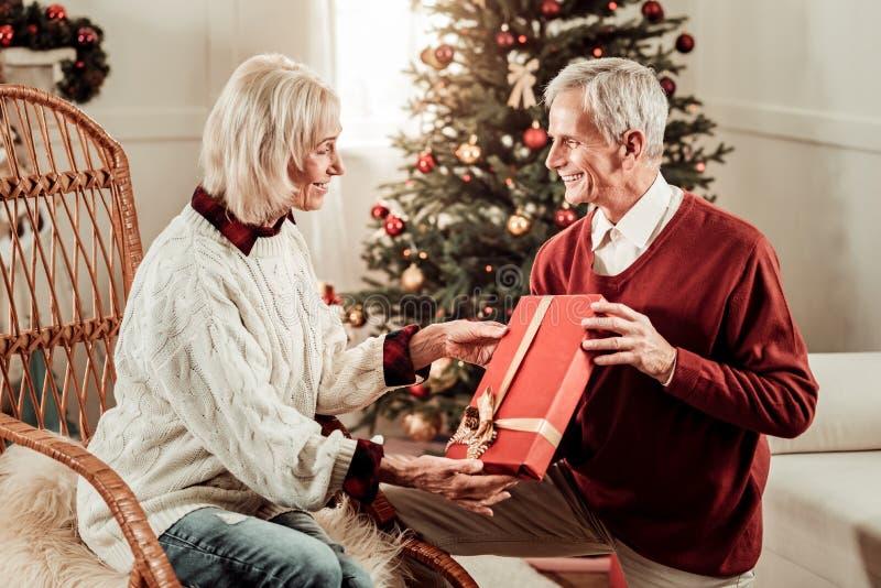 Satisfied sorprendió a la mujer que sentaba y que tomaba un presente fotografía de archivo
