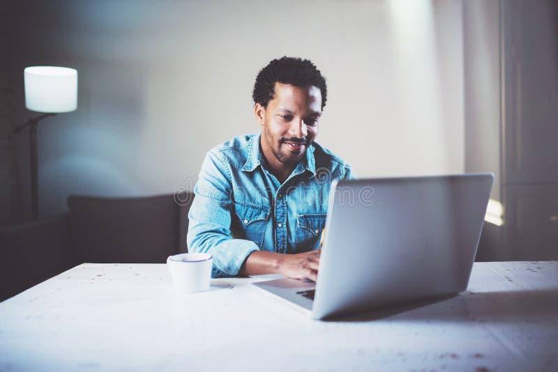 Satisfied uppsökte den afrikanska mannen som använder bärbara datorn på den coworking studion på trätabellen Begrepp av mobilen f arkivbilder
