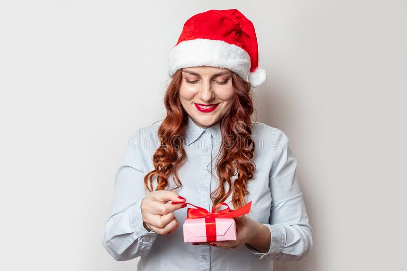 Satisfied young girl with curly hair and a red santa hat on her head holds a gift box and smiles against a gray wall. New Year. Noel royalty free stock photography