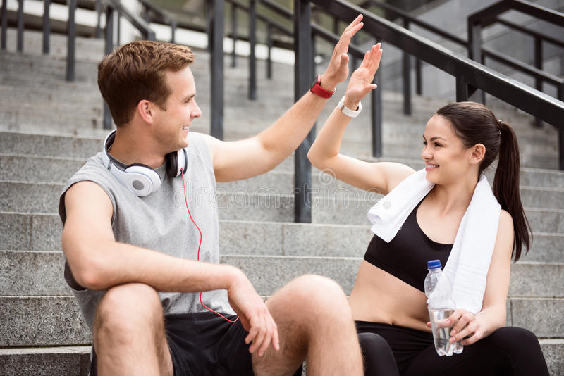 Satisfied young man and woman after training. Give me five. Contended young men giving five to lovely young women while sitting on the stairs after doing sports royalty free stock photos